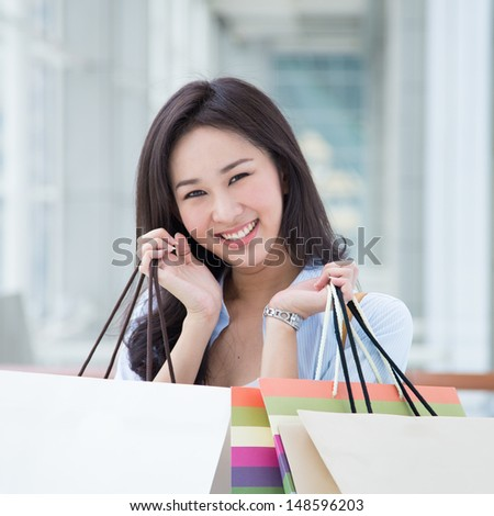 Happy young Asian woman shopping.
