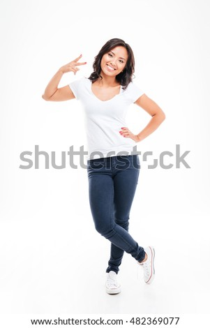 Happy young asian woman showing two fingers or victory gesture isolated on a white background