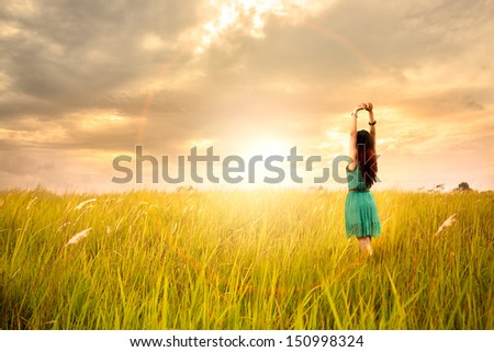 Happy young asian woman standing in meadows with sunset - stock photo