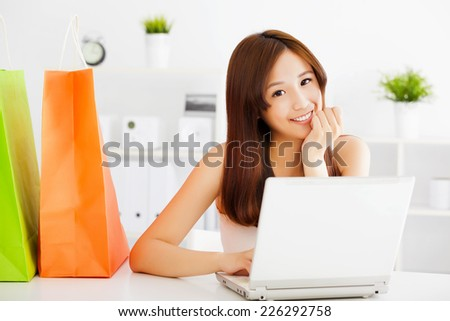 happy young asian woman using a laptop with bags. shopping on line concept