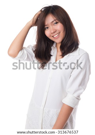 Happy young asian  woman with positive emotion, wearing white dress and playing with her hair,isolated on white background