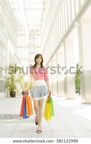 Happy young Asian woman with shopping bags walking outside the mall. Beautiful golden sunlight at background. - stock photo