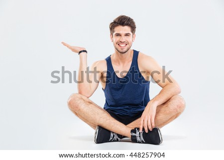 Happy young athletic man sitting with legs crossed and holding copyspace on palm over white background - stock photo