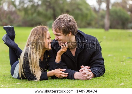 Happy young attractive couple portrait, looking each other on the grass - stock photo