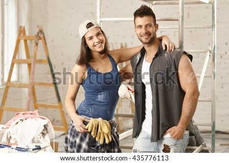 Happy young attractive couple renewing home, smiling happy.