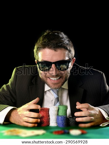 happy young attractive man grabbing and protecting poker chips with his hands after winning bet gambling on table with playing cards on green felt at Casino isolated on black background - stock photo