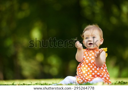 happy young baby child sittng on grass on beautiful summer day in park - stock photo