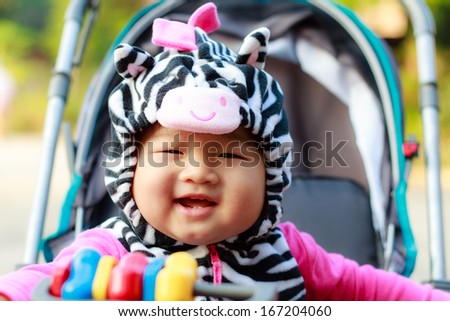 Happy young baby sitting in the baby carriage - stock photo