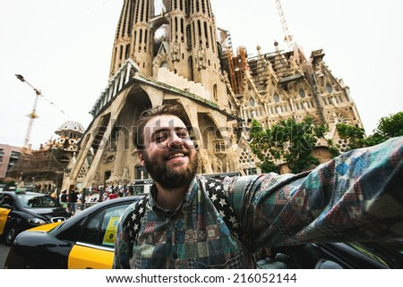 Happy young bearded male tourist looking at camera and taking selfie self-portrait in front of Sagrada Familia while traveling in Barcelona, Spain. - stock photo