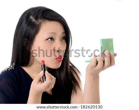 happy young beautiful asian american with red lipstick and mirror making up painting her lips and dressing up isolated on white background in glamour and fashion concept - stock photo