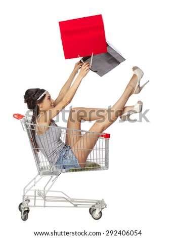 Happy young beautiful brunette woman sits in an empty shopping cart with a red bag, isolated on white background - stock photo