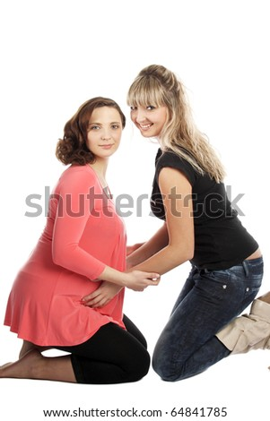 happy young beautiful girl embracing her pregnant sister
