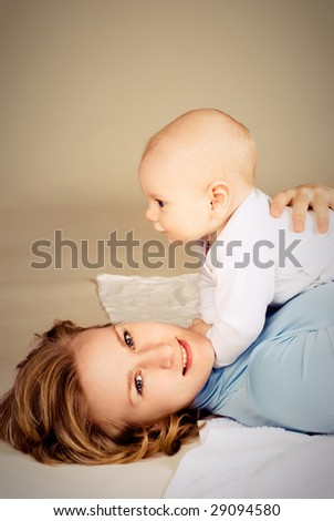 happy young beautiful mother with her little baby on the floor