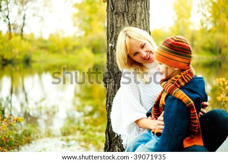 happy young beautiful mother with her little son in the park (focus on the woman) - stock photo