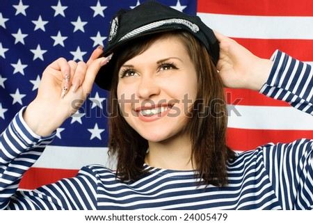 happy young beautiful sailor standing near the American flag