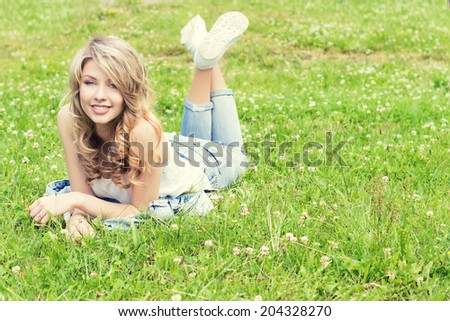 happy young beautiful sexy girl lying on the grass and smiles in jeans in a Sunny summer day in the garden - stock photo