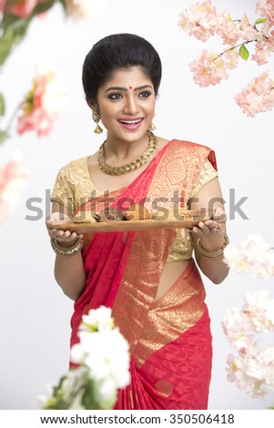 Happy young beautiful traditional Indian woman in traditional saree, holding fresh homemade cookies and sweets for festival in flower garden. - stock photo
