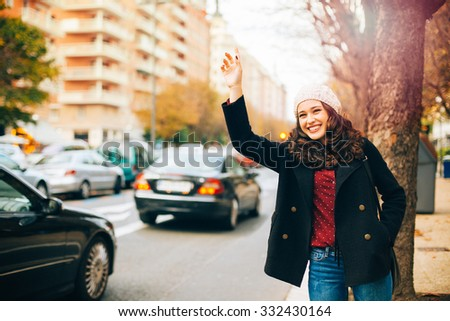 Happy young beautiful woman calling for a taxi with arm raised in the city in autumn - stock photo