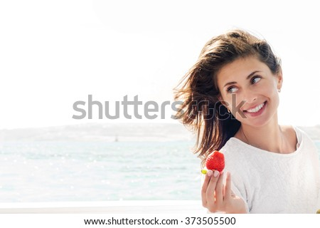 Happy young beautiful woman eating strawberry on the sea, smiling. Summer photo. High key photo. - stock photo