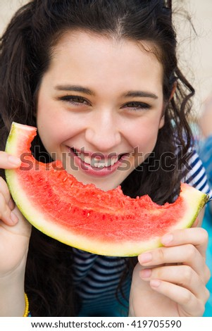Happy young beautiful woman eating watermelon on the beach - stock photo