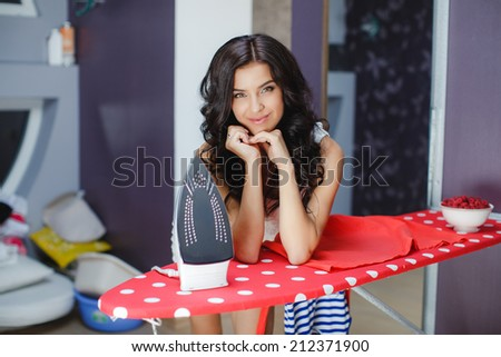 Happy young beautiful woman ironing clothes. Housework. Young beautiful woman ironing clothes in room. woman with iron, looking at camera and smiling - stock photo