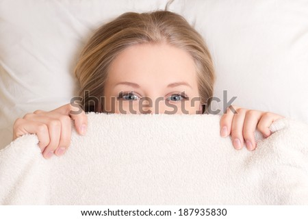 happy young beautiful woman lying in bed under blanket - stock photo