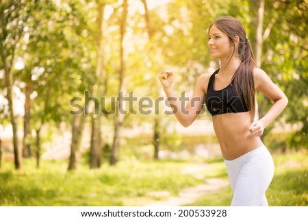 Happy young beautiful woman running in the park