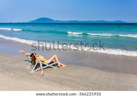 Happy young beautiful woman sunbathing in a bikini on beach chair, dream come true