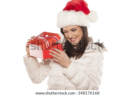 Happy young beautiful woman with a Santa Claus cap, peeking into a gift box