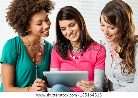 Happy Young Beautiful Women Looking and playing with Digital Tablet