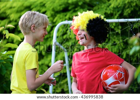 Happy young belgian boys having fun supporting Red Devils during european football championship EURO 2016. Kids in Belgian national tricolour painting flags on their face and playing soccer outdoors.
