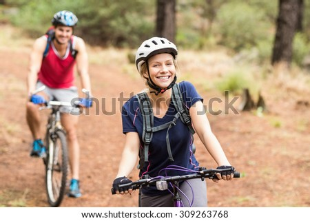 Happy young biker couple looking at camera in the nature - stock photo