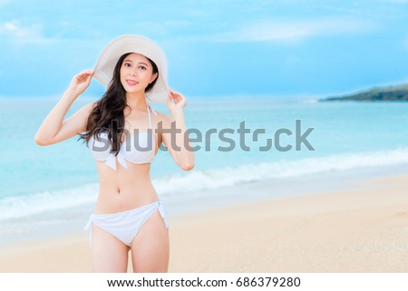 happy young bikini woman going to island country travel enjoying seaside view and looking at camera taking personal journey photo.