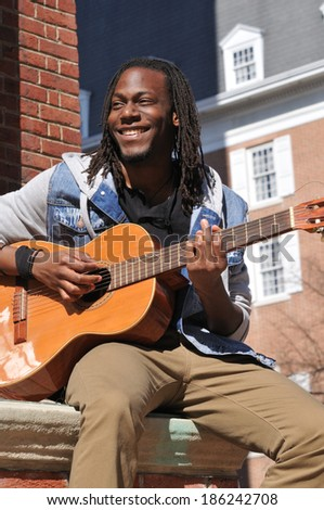 happy young black man playing the guitar in the city - stock photo