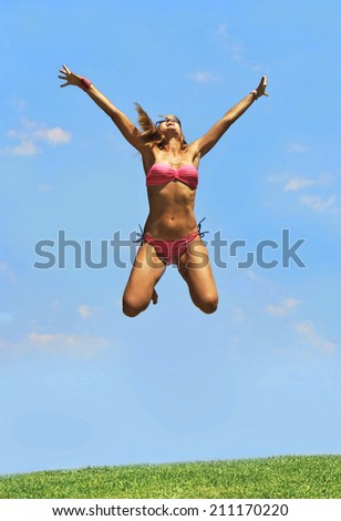 happy young blond attractive woman in pink bikini jumping to the air free on cyan blue summer sky in vitality , fitness , freedom and healthy lifestyle concept