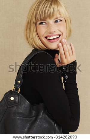 Happy young blond businesswoman laughing in studio - stock photo