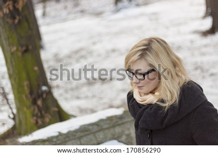 Happy young blond girl in park - winter time. - stock photo