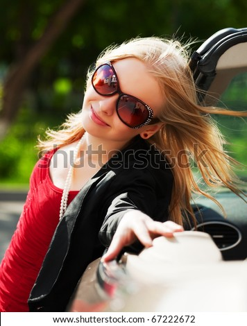 Happy young blond with a convertible car. - stock photo