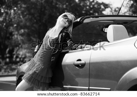 Happy young blond with a new car - stock photo