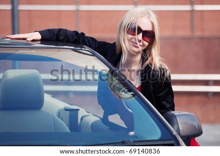 Happy young blond with a new convertible. - stock photo