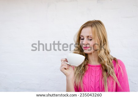 Happy young blond woman drinking hot tea or coffee and looking joyful over pin brick wall copy space background - stock photo