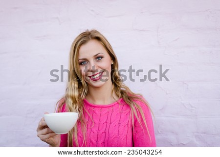 Happy young blond woman drinking hot tea or coffee and looking joyful over pink brick wall copy space background - stock photo