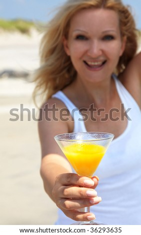 Happy young blond woman drinking orange juice cocktail close up - stock photo