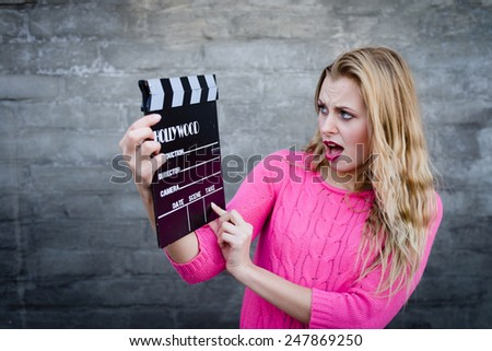Happy young blond woman in pink knitted sweater with cinema clapper board looking surprised over brick wall copy space background - stock photo