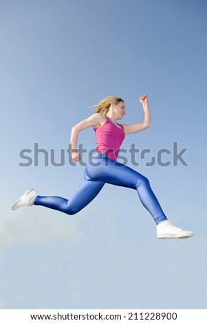 happy young blond woman jogging - stock photo