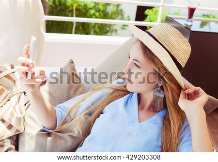 Happy young blond woman taking smartphone selfie photo with smart phone on outdoor patio sofa furniture. Beautiful woman at hotel resort terrace smiling for picture enjoying modern luxury living - stock photo
