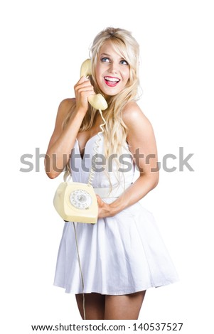 Happy young blond woman talking hot gossip during a retro telephone conversation, white background