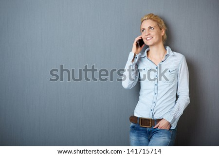 Happy young blond woman using mobile phone against blue background - stock photo