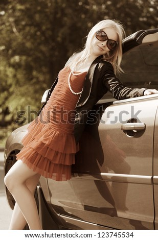 Happy young blond woman with a new car - stock photo