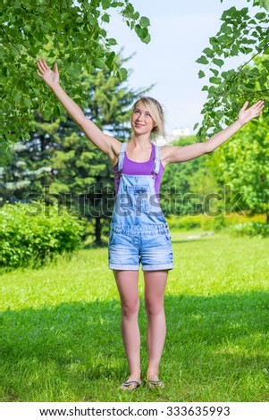 Happy young blond woman with arms outstretched